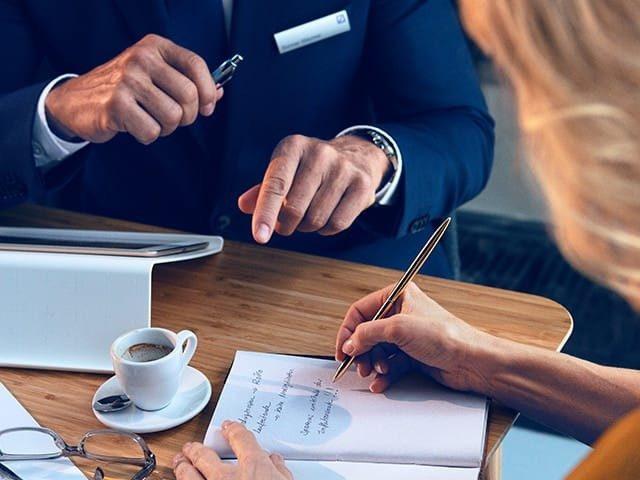 Frau und Bankberater gehen Checkliste des Kreditantrags durch