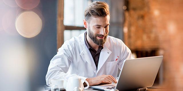 Arzt sitzt am Arbeitsplatz vor dem Computer