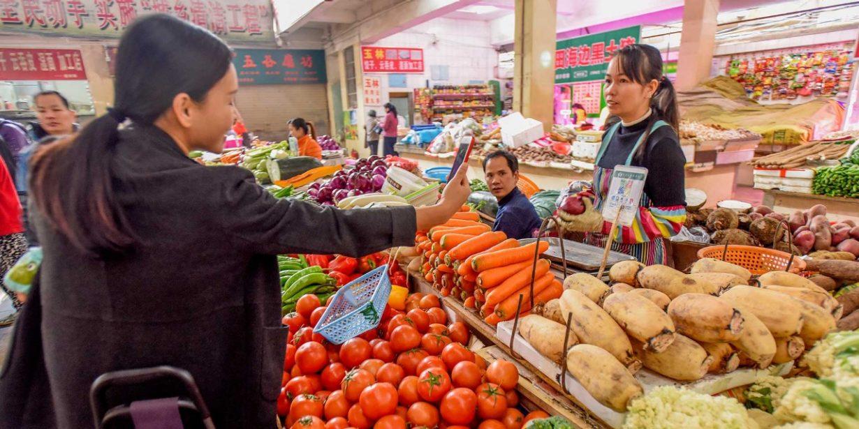 Junge Frau kauft Gemüse am Markt