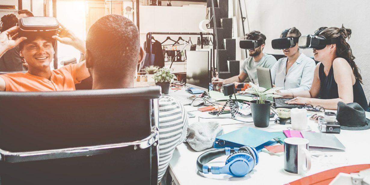 Eine Gruppe junger Menschen sitzt um einen Tisch und trägt teilweise VR-Brillen