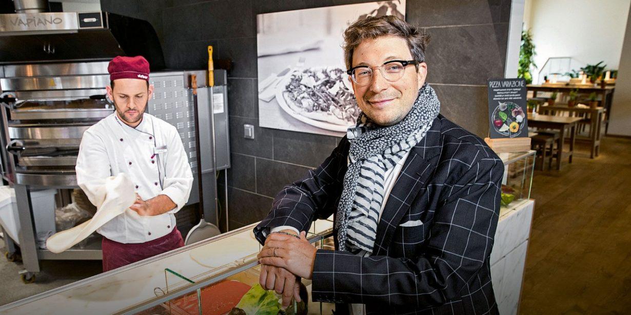 Mann am Tresen einer Vapiano-Filliale mit Koch im Hintergrund